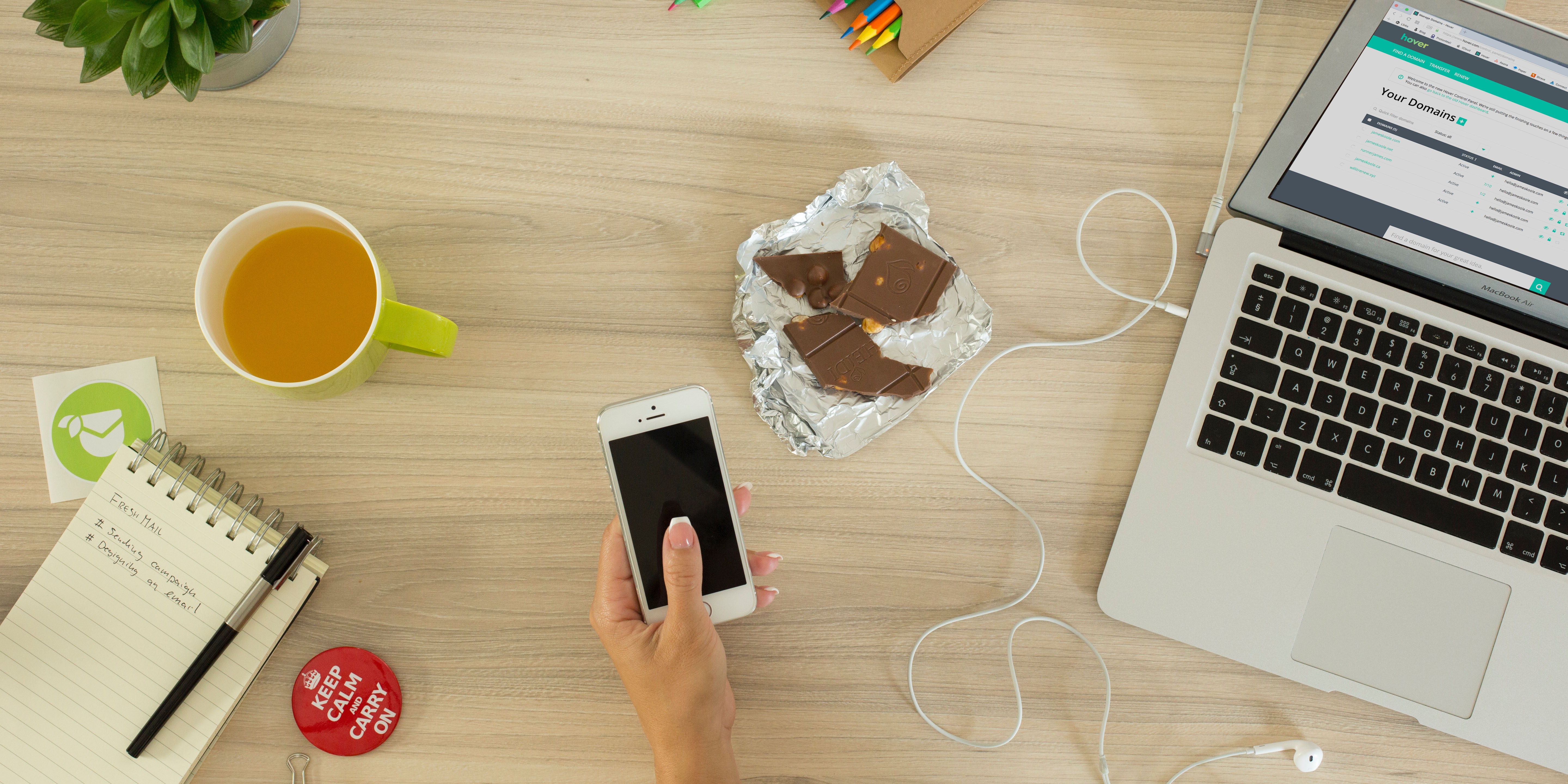 A person using a phone and a laptop on a cluttered desk. And there's chocolate.