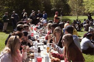 several people gather at picnic tables at the fireside conference