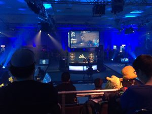 A live eSports audience sites in a blue-lit arena