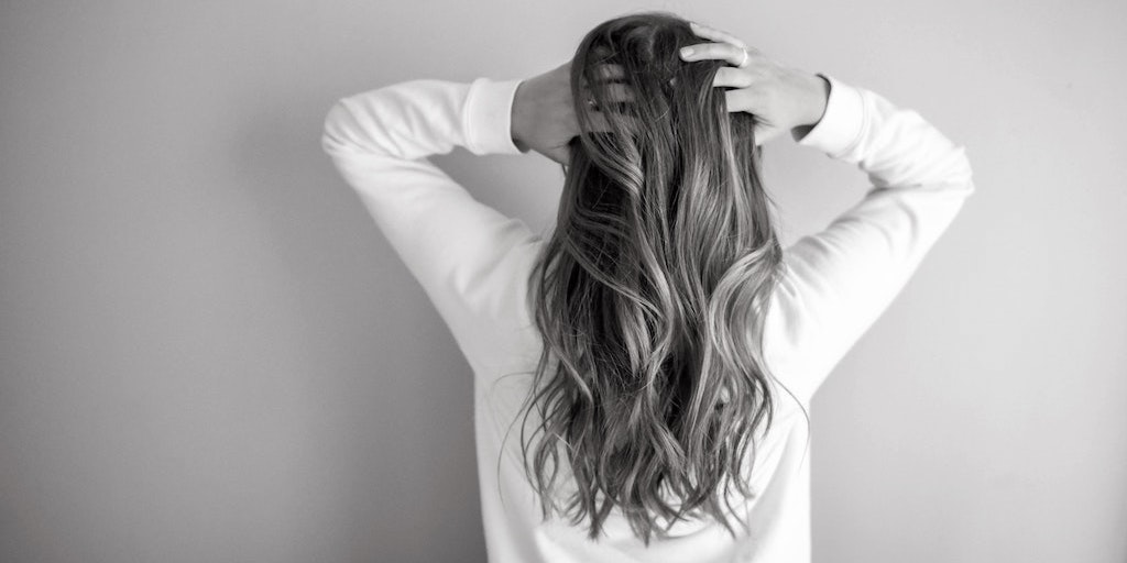 A person with long hair standing with back to us