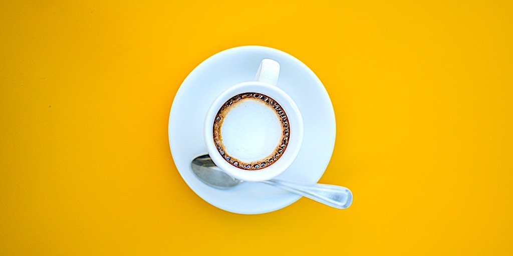 A cup of coffee against a stark yellow background