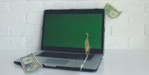 most expensive domain name sold - a laptop with money raining down around it