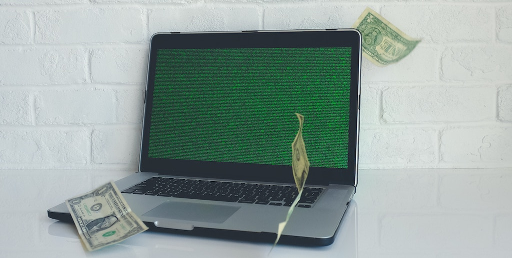 a laptop with money falling around it