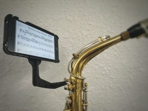 A device holds a phone to a saxophone