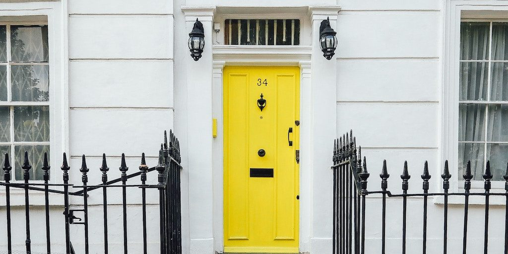 real estate domain name - a house with a bright yellow door