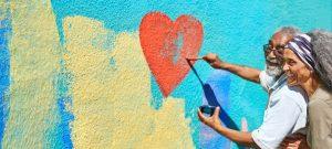 A couple painting a heart on a large wall mural