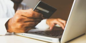 Here are five tips on starting a business during an economic slowdown. Image of a person holding a credit card while typing on a laptop
