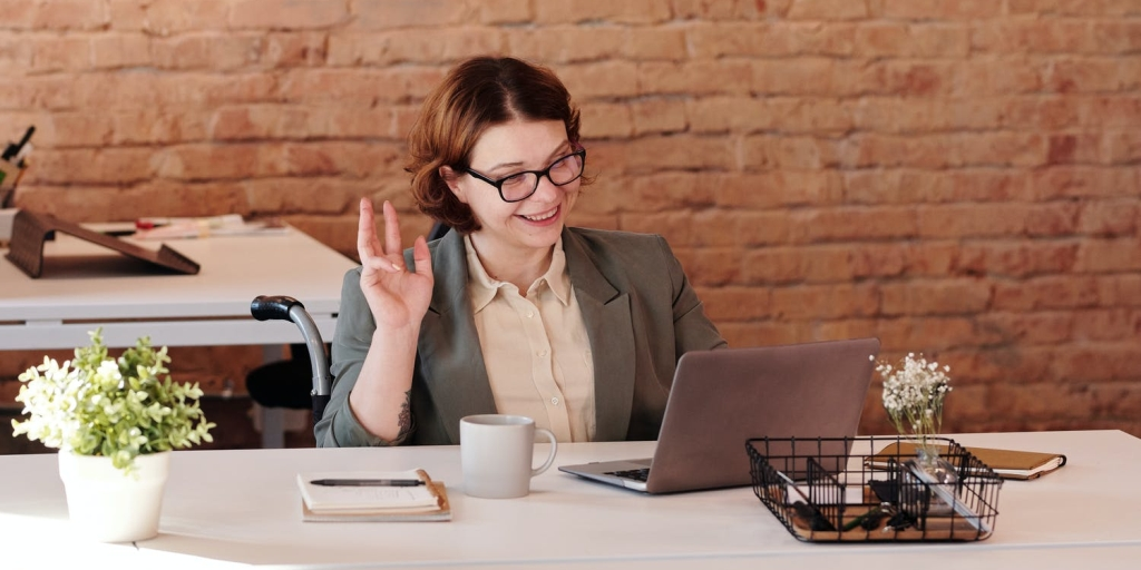 A woman doing business online smiling and waving at her laptop screen.