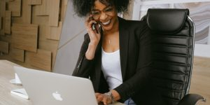 Woman chats on a phone while using a laptop