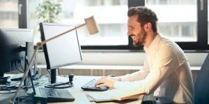 A person at a desk is smiling because they can point a domain anywhere with Hover