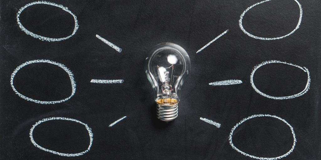 A light bulb rests on black paper with drawn lines and circles radiating from it representing small business ideas