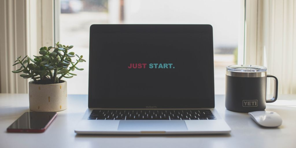 "Laptop screen reads ""just start"" an encouragement to launch MVP"