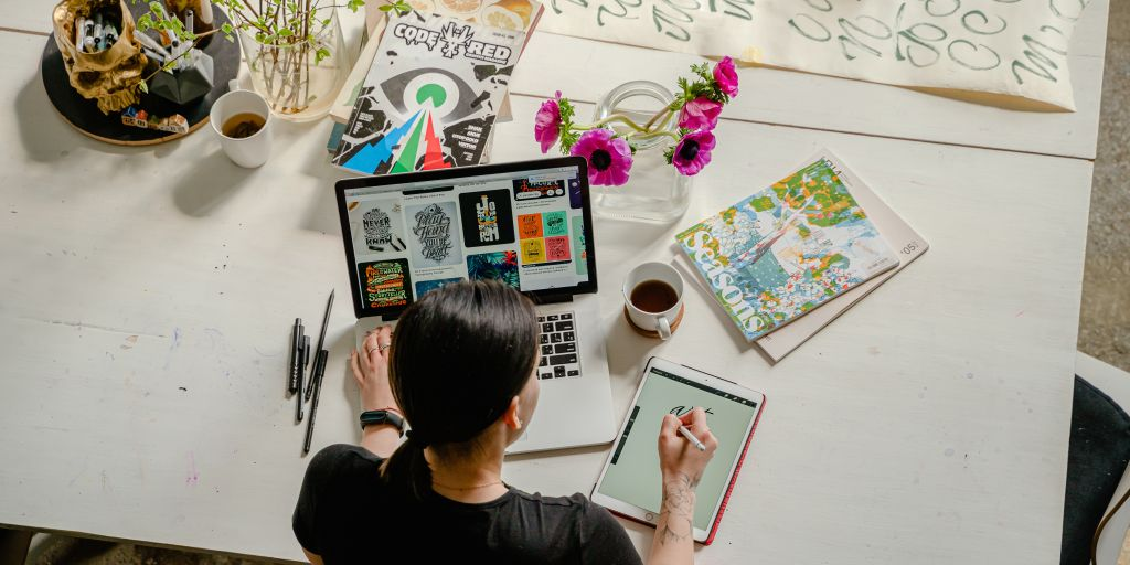 A graphic designer works on their tablet and laptop on a colorfully cluttered desk